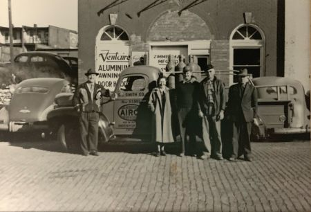 "Sylvester ""S.J."" and Helen Smith, employees, building owner, in front of 1950s S.J. Smith building, truck."